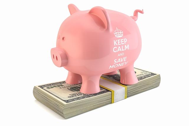 růžové prasátko stojí na balíku peněz